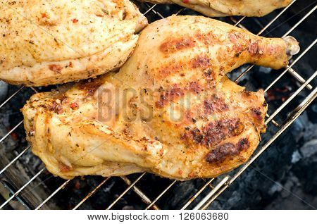 The chicken half roasted over a fire