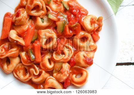 Tortellini Primavera Parmesan In Marinara Sauce On Wooden Rustic Background