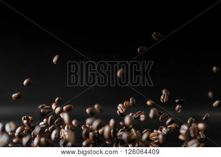 a lot of roasted coffee beans flying in the air