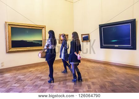 SAINT PETERSBURG, RUSSIA - APRIL 11, 2016: Girls looking at paintings  Arkhip Kuindzhi at the State Russian museum. The museum is the largest depository of Russian fine art in St. Petersburg