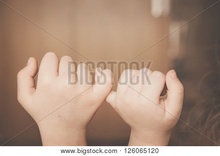 childs hands promise indoor in brown tones isolated