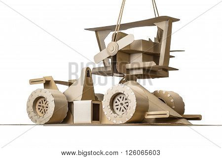 Photo of cardboard racing car and plane on white background.