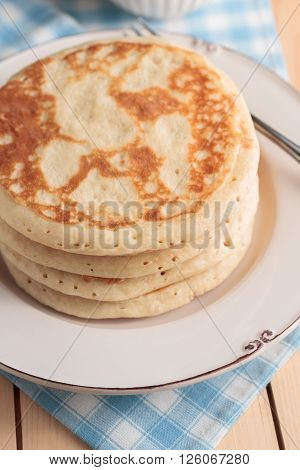 Buttermilk pancakes with shallow focus subdued morning lighting and breakfast setting