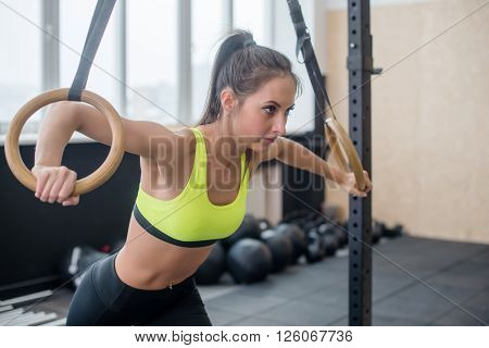 side view of a fit woman doing push-ups with gymnastic rings in gym.