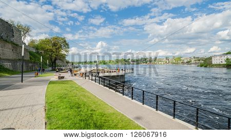 NARVA ESTONIA - MAY 22 2015: Narva River embankment with vacationers people and the border of Russia and the European Union