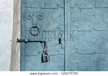 Aged architectural background - old steel grey door with plates rivets and old door handle formed as stylized lily.