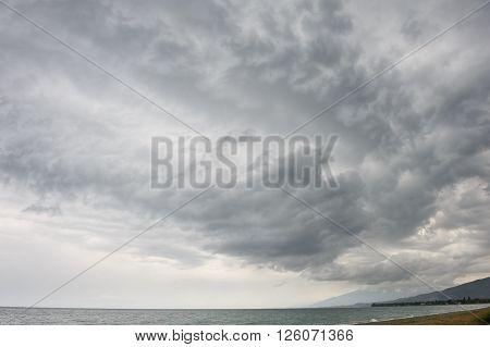 rainstorm, heavy overcast raiclouds over the sea beach