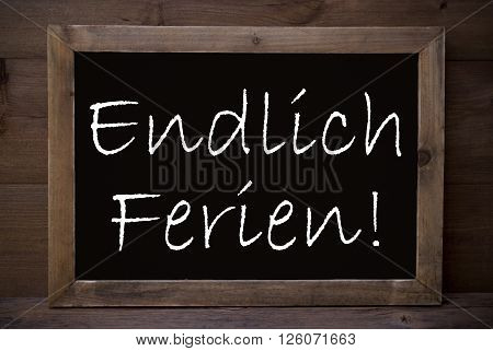 Brown Blackboard Or Chalkboard With German Text Endlich Ferien Means Happy School Vacation As Greeting Card. Wooden Background. Vintage Rustic Style.