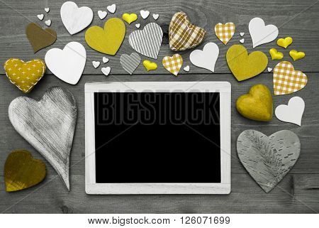 Chalkboard With Copy Space For Advertisement. Many Yellow Textile Hearts. Wooden Background With Vintage, Rustic Or Retro Style. Black And White Image With Colored Hot Spots.