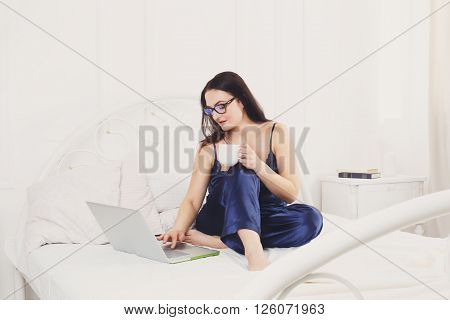 Middle aged woman with laptop in white bed. Woman in eyeglasses typing on gadget pc. Morning coffee. Beautiful woman in blue nightwear at bed surfing internet at her computer. High key. Soft tone