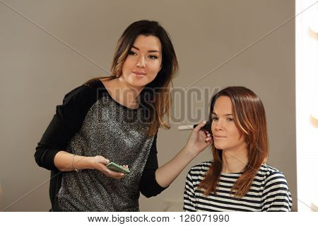 Makeup artist applies powder on the client's face in salon. Beautician holding cosmetology brush near the face of the girl.