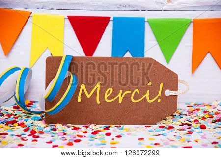 Label With French Text Merci Means Thank You. Party Decoration Like Streamer, Confetti And Bunting Flags. White Wooden Background With Vintage, Retro Or Rustic Syle