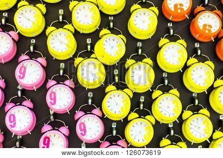 many Pink orange yellow alarmclocks on the wall