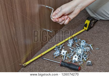 Assembling furniture using allen key close-up hand turning hex wrench in diy furniture.