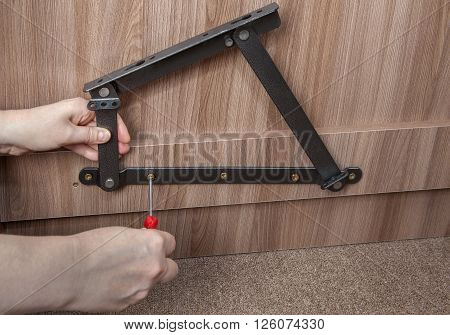 Furniture Installation Installing steel spring bed lift system close-up hands of installer furniture tighten screw using a screwdriver.