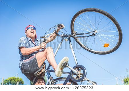 Youthful senior man riding on bicycle and doing a wheelie - Old man acting like a kid