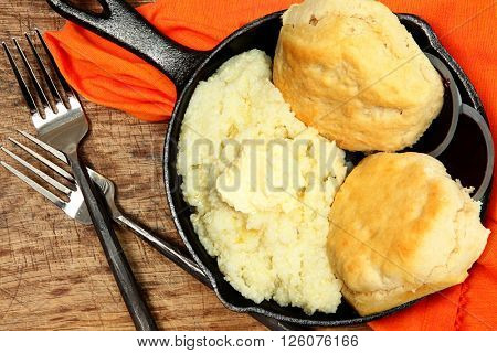 Skillet Grits and Biscuits in cast iron on table.