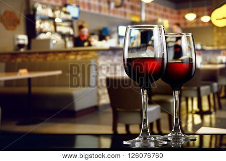Two glasses of red wine on bar counter of restaurant interior