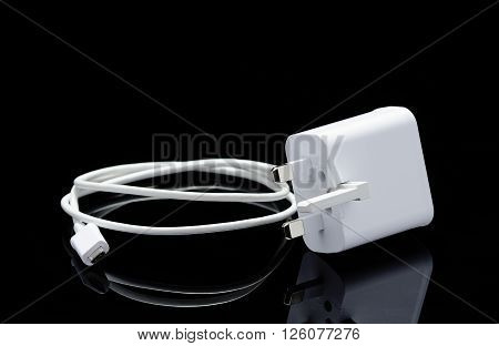 White USB cable for smartphone and its reflection on black background