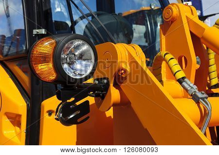 Bulldozer headlight, huge orange powerful construction machine with light equipment also used for tractors, excavators, loaders and other machines, focused on spotlight, selective focus