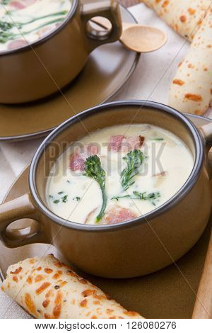 Close up of creamy Broccoli Chowder Soup with beacon potato and broccoli. Cheddar rosemary breadsticks.