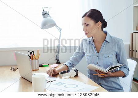 Cheerful woman is using a laptop for work. She is sitting at the desk and holding a writing-pad. The lady is smiling