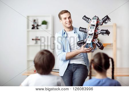 My work. Cheerful overjoyed nice father holding robot and showing it to his kids while having fun together