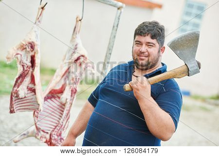 butcher with axe and sheep carcass meat