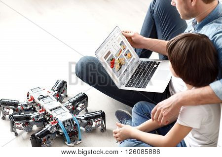 My dear. Pleasant loving father sitting on the floor with   his son and using laptop while embracing him