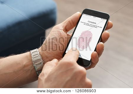 Kiev Ukraine - March 06 2016: Man using touch ID scanner of fingerprints on iPhones 6 developed by Apple corporation. Allows users to unblock the smartphone and to make purchases.