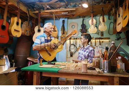 Small family business and traditions: old grandpa with grandson in lute maker shop. The senior artisan gives teaches how to play classic guitar to the boy who looks carefully at the instrument