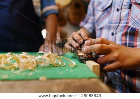 Small family business and traditions: old grandpa with grandson in lute maker shop. The senior artisan teaches to the boy how to chisel wood to make a guitar. Closeup of hands