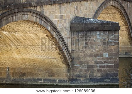 Detail of the arches of an historic bridge across the Arno river Florence Italy
