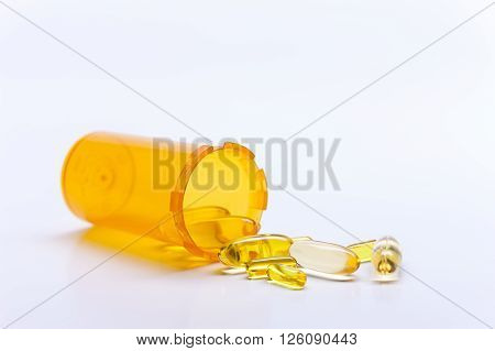 Assorted pills from a bottle. A close up of pills spilling out from a pill bottle on its side.