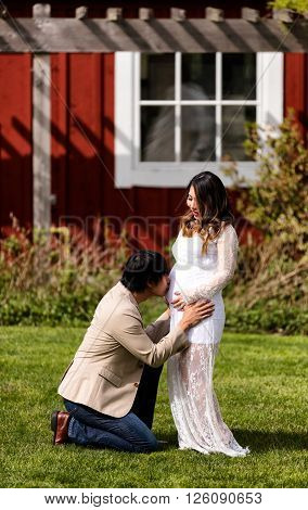 Husband kissing abdomen of expecting mom while kneeling in front of her on grass.
