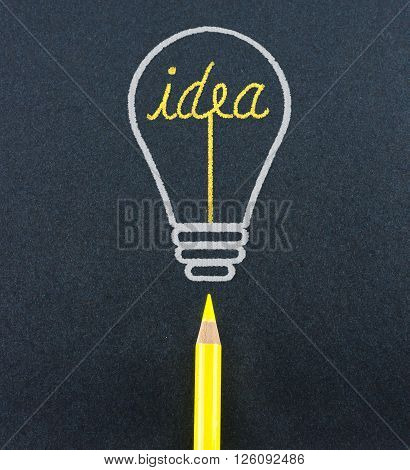 Yellow pencil sketch in light bulb shape ignite the idea word on black craft paper Creativity concept