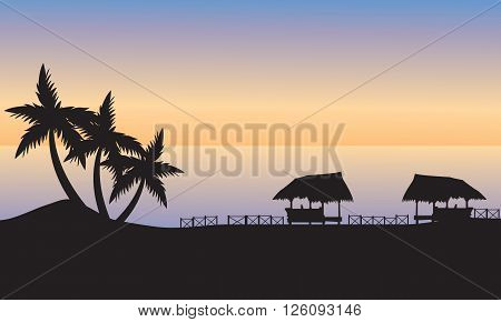 Gazebo and palm on the ocean shore at sunset