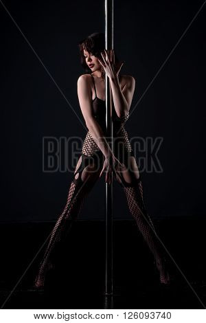Stripper dressed in fishnet bodysuit posing with pole.