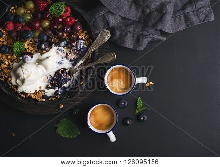 Healthy breakfast. Oat granola crumble with fresh berries, seeds and ice-cream in iron skillet pan, coffee cups on dark wooden board over black backdrop, top view, copy space