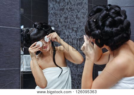 Lovely girl joking with cotton pad in the bathroom. Morning makeup.
