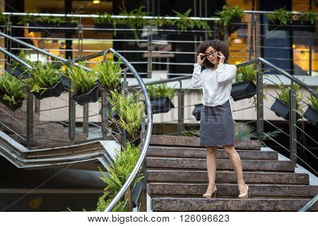Asian business woman talking on mobile standing in the stairwell.