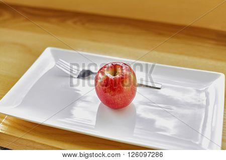 Red Apple On White Plate With A Fork