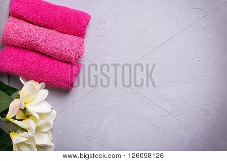 Spa or wellness setting. Set of pink bath towels and white tropical plumeria flowers on grey textured background. Selective focus. Place for text.