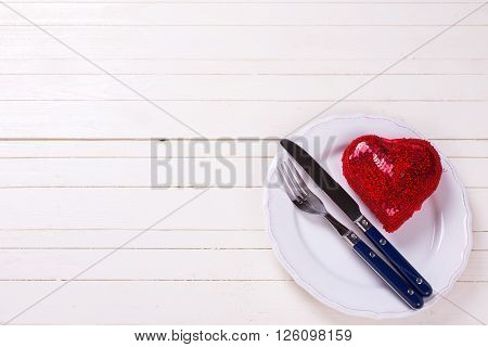 Romantic table setting. Decorative red heart knife and fork on white plate on white wooden background. Selective focus. Place for text.