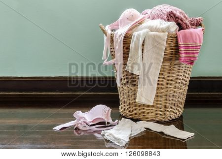 Clothes and underwear in rattan basket on the floor.