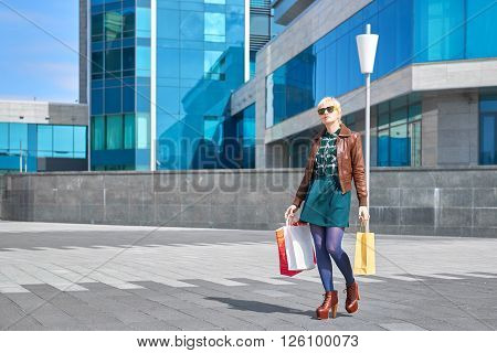 Beautiful woman in sunglasses walking with shopping bags on the street
