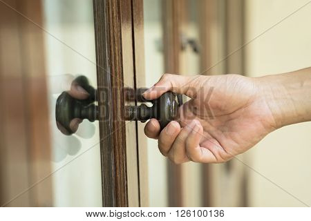 close up hand hold handle of wood door