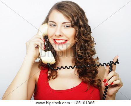 beautiful curly woman  talking on white vintage telephone