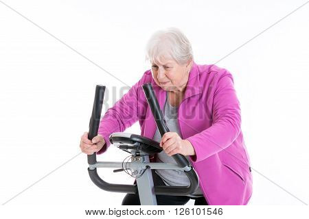 gray-haired female senior with thumb up train with fitness machine