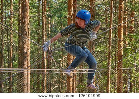 Woman having fun in adventure rope park